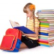 Schoolgirl with backpack reading pile of books. - Stok fotoğraf