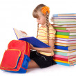 Schoolgirl with backpack reading pile of books. - 