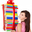 Girl holding pile of book. - Stock Photo