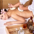 Young woman on massage table in beauty spa. - Stock Photo