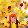 Photo: Girl in autumn orange hat with yellow leaves. Outdoor.