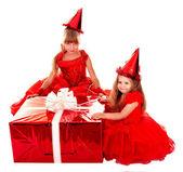 ребенок в шляпе партии с рождественский подарок красное поле. — Стоковое фото