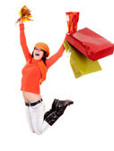 Girl in autumn orange sweater with leaf, shopping bag jump. — Stock Photo