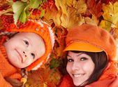 Happy family with child on autumn orange leaves. — Стоковое фото