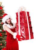 在圣诞老人的帽子和杉木树中与红色礼品盒圣诞女孩. — 图库照片