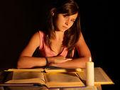 Meisje leesboek met kaars. — Stockfoto