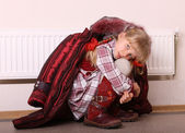 Girl in coat warm near radiator. Crisis. — Stock Photo