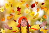 Girl in autumn orange hat with yellow leaves. Outdoor. — Stok fotoğraf