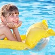 Child swimming on inflatable beach mattress. - Stock Photo