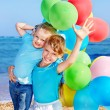 Children playing with balloons at the beach — Stock Photo #5187656