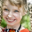 Happy child with butterfly on neck. — Stock Photo