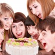 Photo: Group of happy young with cake.
