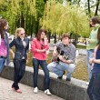 Group of in city park listen music. — Foto Stock