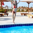 Girl with goggles and red swimsuit jump in swimming pool. — Stock Photo #5188121
