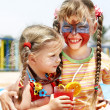 Stock Photo: Children with face painting drinking juice.