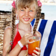 Child on beach drinking cocktail. - Stock Photo