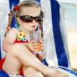 Child in glasses and red bikini drink juice. - 
