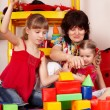 Children  with  block and senior woman in play room. — Stock Photo