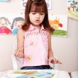 Child paint picture in preschool. -  