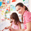 Child painting with teacher in preschool. — Stock Photo #5188296