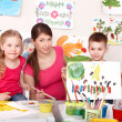 Children painting with teacher in art class. - Stock Photo