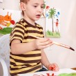 Child paint picture in preschool. - Zdjcie stockowe