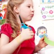 Child with scissors cut paper in play room. — Stock Photo