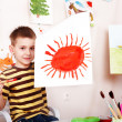 Child with picture and brush in play room. -  