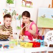 Child with teacher draw paints in play room. — Стоковая фотография