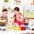 Child with teacher draw paints in play room. — Foto de Stock