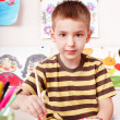 Child with picture and brush in play room. — Stock fotografie