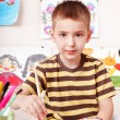Child with picture and brush in play room. — Foto de Stock