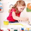 Stock Photo: Child with brush draw picture in play room.
