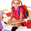 Happy sitting schoolgirl in eyeglasses  with  pile of books. - Stock Photo