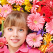 Child lying on the flowers. — Stock Photo