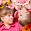 Cute child lying head to head on the flower. — Stock Photo