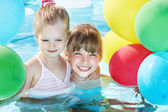 Children playing with balloons in swimming pool. — Stock Photo