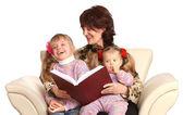 祖母和两个孙女阅读本书. — 图库照片