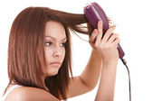 Beautiful girl with hair straightener. — Stock Photo