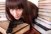 Girl with heap book and weapon. — Stock Photo
