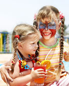 Children with face painting drinking juice. — Stock Photo