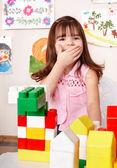 Dziecko z bloku drewna w sali zabaw. — Zdjęcie stockowe