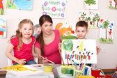 Children painting with teacher in art class. — Stock Photo