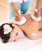 Girl having Thai herb compress massage. — Stock Photo