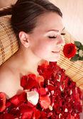 Young woman in rose petal swim water. — Stock Photo