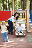 Mother with children on slide outdoor. — Foto Stock