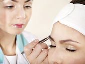 Tweezing eyebrow by beautician. — Stock Photo