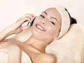Woman on massage table call by phone. — Stock Photo