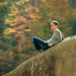 Stock Photo: Young hiker relaxing on rock