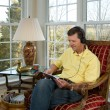 Stock Photo: Boomer reading on tablet computer